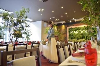 マルーン色の絨毯は上品さを、一面に飾ったグリーンはかわいらしさを演出/