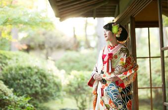大きな松が立ち並ぶ、美しく手入れされた日本庭園を背景に