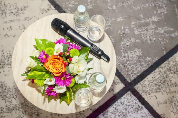 小さい丸テーブルに置かれたマイク、水、花