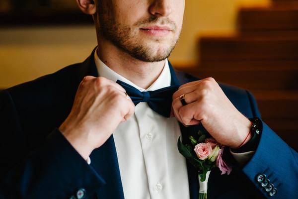 蝶ネクタイを結ぶ新郎