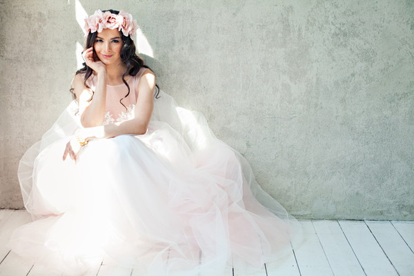 ほほえみしゃがむピンクのドレスを着た女性