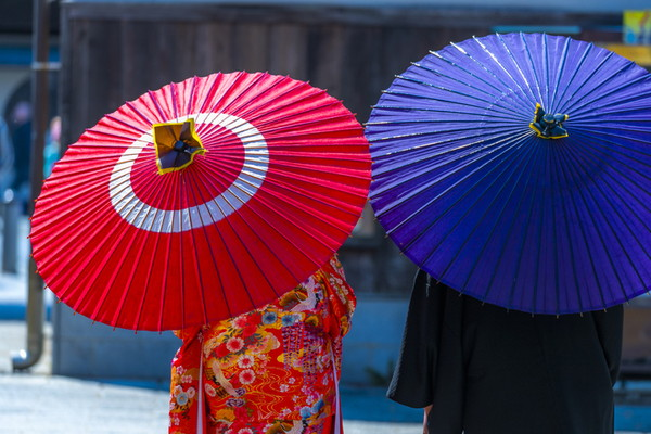 和傘を差す新郎新婦